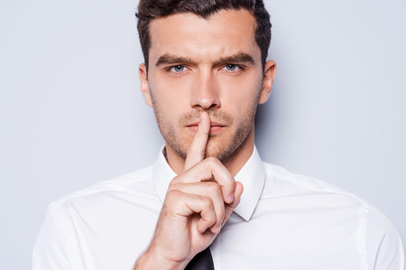 Guarde silencio! Hombre joven confidente en camisa blanca que mira la cámara y la celebración de un dedo en los labios mientras está de pie contra el fondo gris