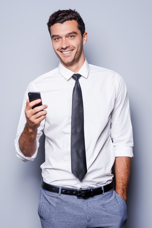 Businessman with mobile phone. Confident young man in shirt and tie holding mobile phone and smiling while standing against grey background