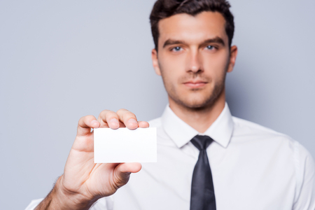 Copy space on his business card. Confident young man in shirt and tie showing his business card while standing against grey background photo