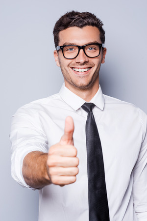 Good job! Happy young man in shirt and tie showing his thumb up and smiling while standing against grey background photo