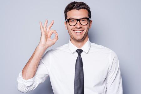 모든 것이 OK입니다! 회색 배경에 서있는 동안 셔츠와 넥타이에 행복 한 젊은 사람이 확인 서명 몸짓과 미소