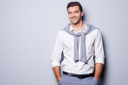 sex symbol: Handsome in style. Cheerful young man in smart casual wear looking at camera and holding hands in pockets while standing against grey background Stock Photo