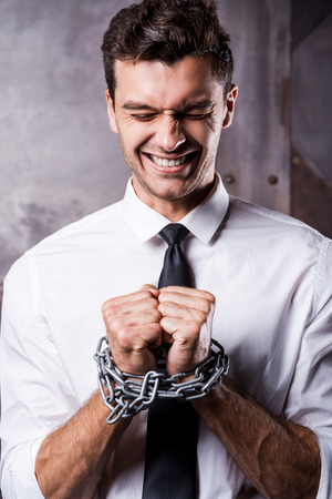 Businessman trapped in chains. Frustrated young businessman grimacing while being trapped in chains photo