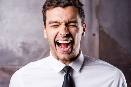 Stressed businessman. Furious young man in shirt and tie shouting and keeping eyes closed photo