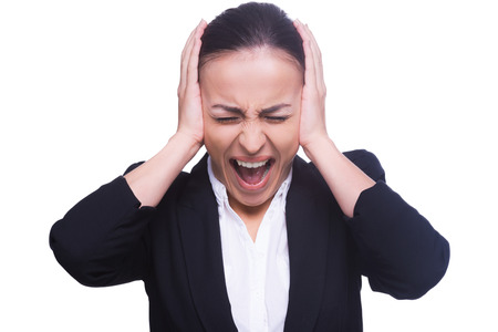 emotional stress: Emotional stress. Frustrated young woman in formal wear covering ears with hands and keeping eyes closed while standing isolated on white Stock Photo