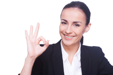 ok sign: Gesturing OK sign. Happy young woman in formal wear gesturing OK sign and smiling while standing isolated on white