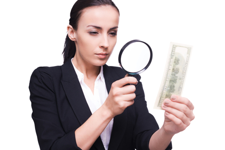 Finance inspector. Confident business woman looking through magnifying glass at one hundred dollar bill  photo
