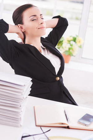Chill time. Side view of cheerful young business woman holding head in hands and keeping eyes closed while sitting at her working place photo