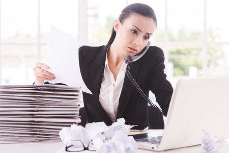 Busy working. Confident young woman in formalwear with documents and talking on the telephone while sitting at her working place photo
