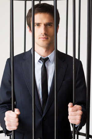 white collar crime: White collar crime. Depressed young man in formalwear standing behind a prison cell and looking at camera  Stock Photo