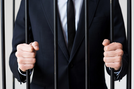 cella carcere: Gli uomini d'affari in carcere. Immagine ritagliata di uomo in formalwear in piedi dietro una cella di prigione Archivio Fotografico