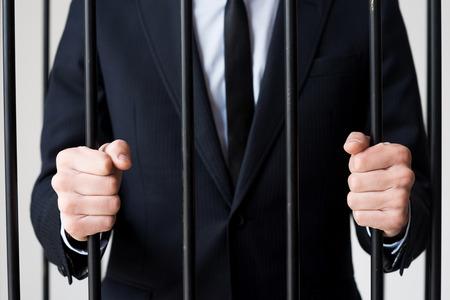 cellule de prison: Les hommes d'affaires en prison. Image recadrée de l'homme dans formalwear debout derrière une cellule de prison