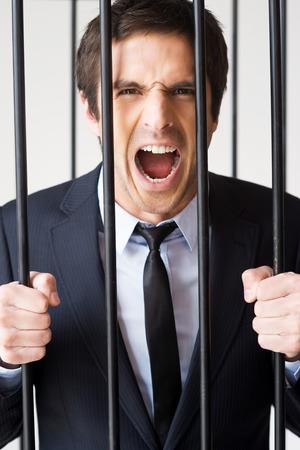 私は有罪ではない !刑務所の独房の後ろに立っていると叫んで正装で猛烈な若い男