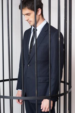 cella carcere: Penale di affari. Depresso giovane uomo in formalwear in piedi dietro una cella di prigione e guardando lontano Archivio Fotografico