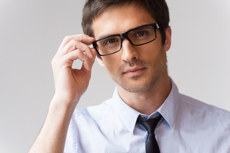 Confident look. Portrait of handsome young man in shirt and tie adjusting his eyeglasses and looking at camera while standing against grey background photo