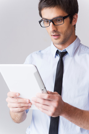 surprised man: It is just amazing! Surprised young man in shirt and tie looking at digital tablet and keeping mouth open while standing against grey background