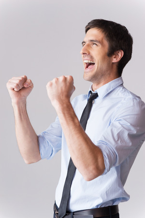 excited man: I did it! Side view of excited young man in shirt and tie gesturing and smiling while standing against grey background