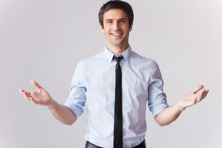 only one man: You are always welcome! Handsome young man in shirt and tie gesturing and smiling while standing against grey background