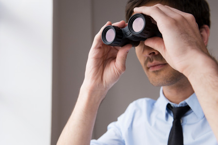 opportunity discovery: Looking for new opportunities. Confident young man in shirt and tie looking through binoculars