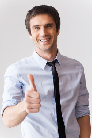 Well done! Happy young man in shirt and tie showing his thumb up and smiling while standing against grey background photo