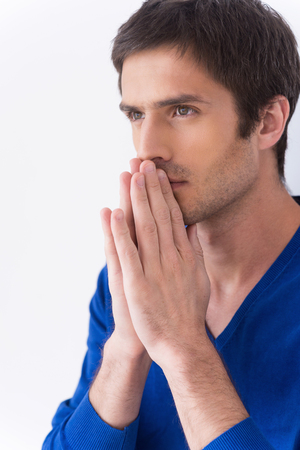 near side: Man praying. Side view of thoughtful young man in white shirt holding hands clasped near face and looking away while standing against grey background Stock Photo