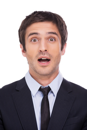 What a surprise! Surprised young man in formalwear staring at camera and keeping mouth open while standing against grey background photo