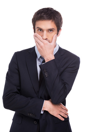 I will keep your secret. Handsome young man in formalwear covering mouth with hand and looking at camera while standing isolated on white background photo