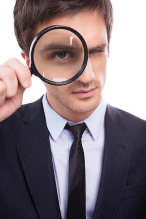 Businessman examining you. Serious young man in formalwear examining you with magnifying glass while standing isolated on white background  photo