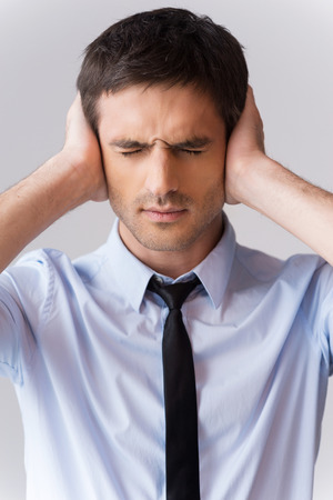 No more word! Tired young man in shirt and tie covering ears with hands and keeping eyes closed while standing against grey background photo