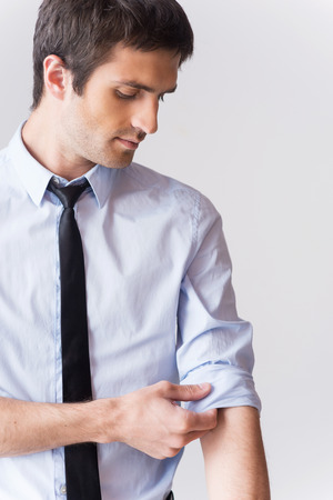 Ready to work. Confident young man in shirt and tie adjusting his sleeve while standing against grey background Stock Photo