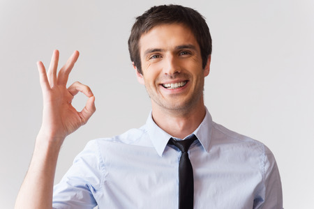 ok sign: Gesturing OK sign. Cheerful young man in shirt and tie gesturing OK sign while standing against grey background
