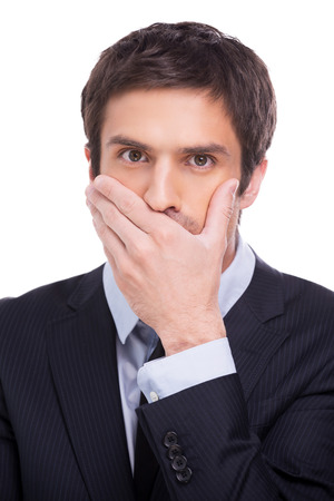 Keeping a secret. Portrait of young man in formalwear covering mouth with hand and looking at camera while standing isolated on white background photo