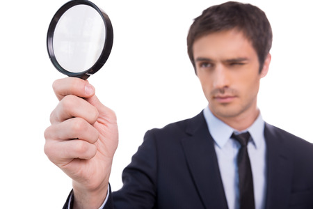 Looking through magnifying glass. Concentrated young man in formalwear looking through a magnifying glass while standing isolated on white background  Stock Photo