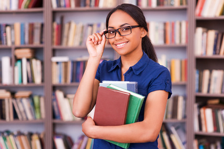 african student: Feeling confident about exams. Cheerful African female student holding books and smiling while standing in library
