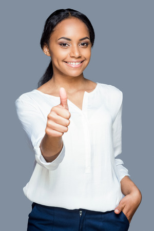 Beauty with thumb up. Waist up of attractive young African woman showing her thumb up and smiling while standing against grey background photo