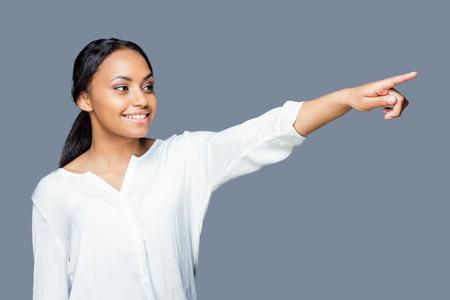 저것 좀 봐! 멀리 가리키고 회색 배경 서있는 동안 웃고 매력적인 젊은 아프리카 여자 스톡 콘텐츠