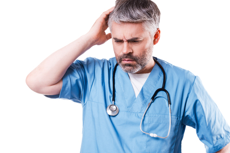 head shots: Depressed surgeon. Side view of depressed mature doctor touching his face with hand and keeping eyes closed while standing isolated on white