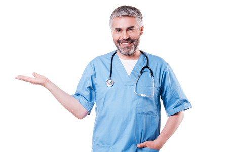 Copy space at his hand. Confident mature surgeon holding copy space in his hand and smiling while standing isolated on white photo