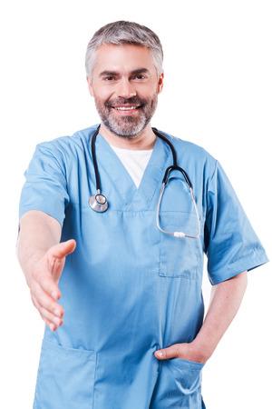 絶対に、私を信頼することができます !青い制服カメラ目線と白で隔離される立ちながら笑顔で幸せな成熟した外科医