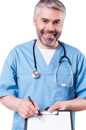 in need of space: That is what you need! Cheerful mature doctor looking at camera and smiling while pointing copy space on his clipboard and standing isolated on white Stock Photo