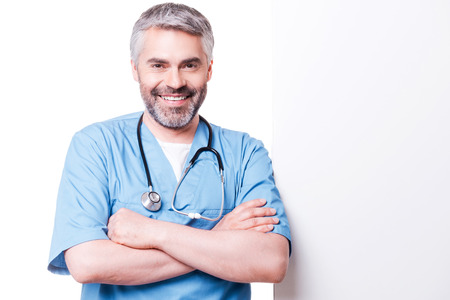 Surgeon leaning at copy space. Confident mature surgeon leaning at copy space and smiling while standing isolated on white Stock Photo