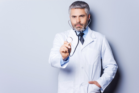 Medical exam. Confident mature grey hair doctor examining you with stethoscope while standing against grey background photo