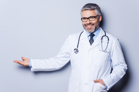mature doctor: Doctor advertising your product. Cheerful mature doctor looking at camera and pointing away while standing against grey background