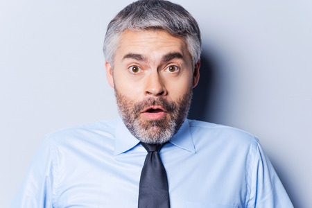 Surprised businessman. Surprised mature man in shirt and tie staring at camera and keeping mouth open while standing against grey background photo