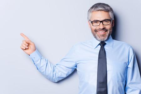 사업가 포인팅 복사본 공간입니다. 행복한 성숙한 남자 셔츠와 넥타이 카메라를 찾고 회색 배경에 서있는 동안 멀리 가리키는 스톡 콘텐츠