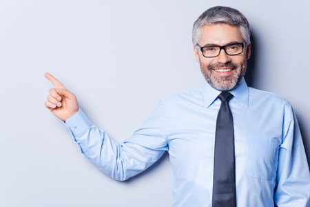 Businessman pointing copy space. Happy mature man in shirt and tie looking at camera and pointing away while standing against grey background Imagens - 29821520