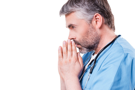 one senior man only: Doctor praying. Side view of mature grey hair doctor holding hands clasped near face while standing isolated on white