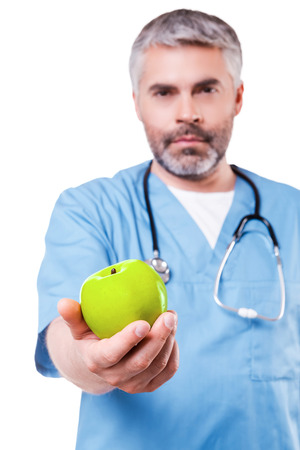 Join healthy lifestyle! Confident mature surgeon in blue uniform stretching out a green apple while standing isolated on white photo