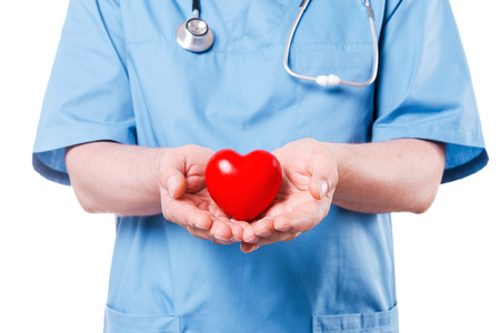 Your heart is in good hands. Close-up of mature cardiology surgeon holding heart shape toy while standing isolated on white