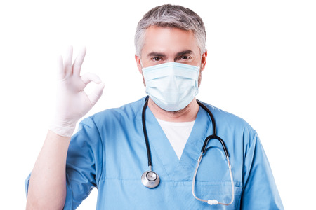ok sign: Surgeon gesturing OK. Mature grey hair doctor in surgical mask and gloves gesturing OK sign while standing isolated on white